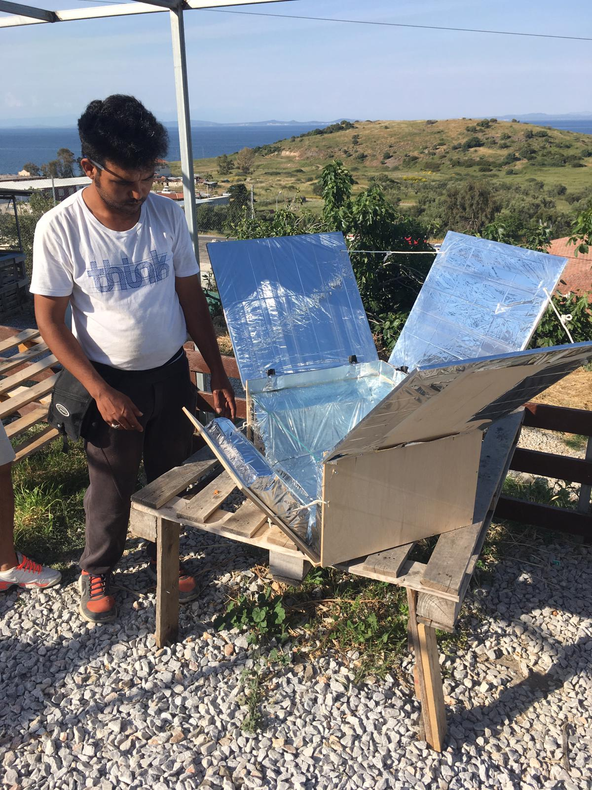 a pic of Mehdi from the makerspace standing by a solar oven made for the rescue boat Mare Liberum